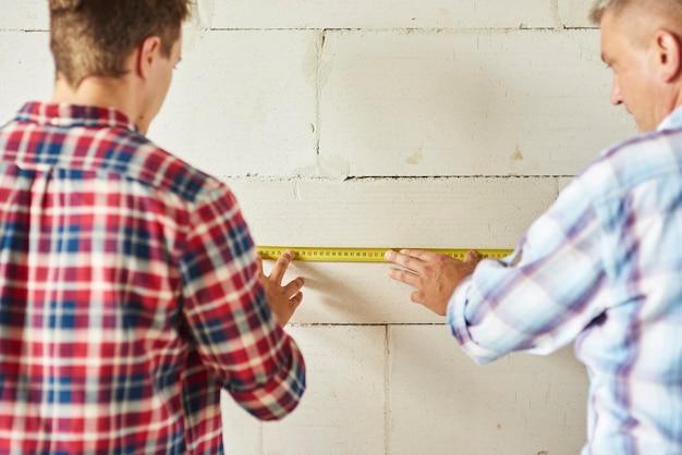若い男と老人が壁を測る