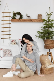 居心地の良いセーターの若い男とかわいいモデルの女の子は、クリスマスのインテリアのために装飾されて抱擁します