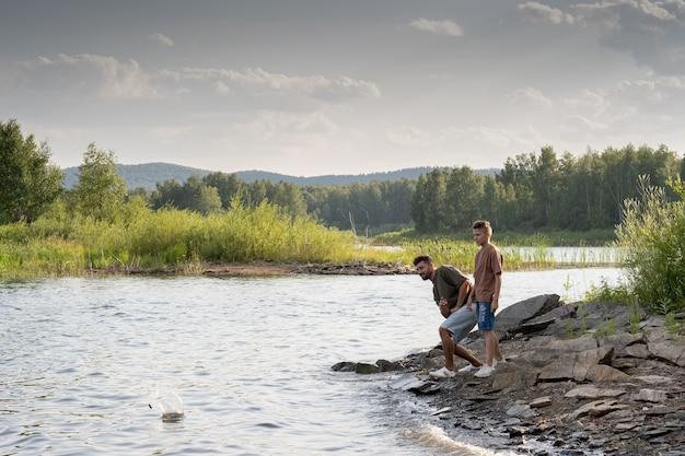 호수에서 시간을 즐기는 젊은 남자와 십 대 소년