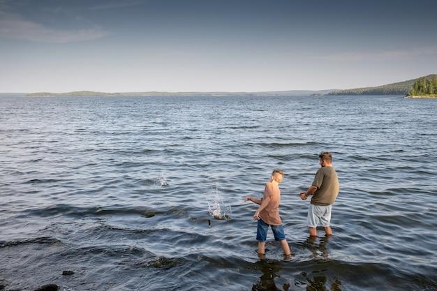 젊은 남자와 10대 소년이 호수에 서서 물에 돌을 던지고 있다