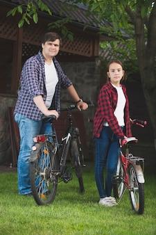젊은 남자와 공원에서 자전거와 함께 포즈를 취하는 십 대 소녀