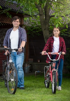 若い男と自転車でポーズをとる10代の少女