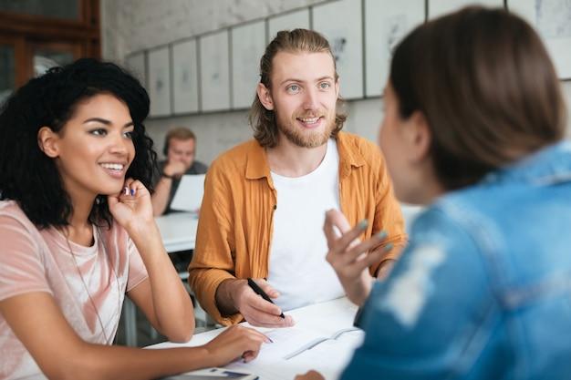 Молодой человек и две женщины работают вместе в офисе