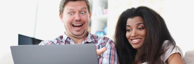 젊은 남녀가 노트북 화면 앞에 앉아 웃고 있다
