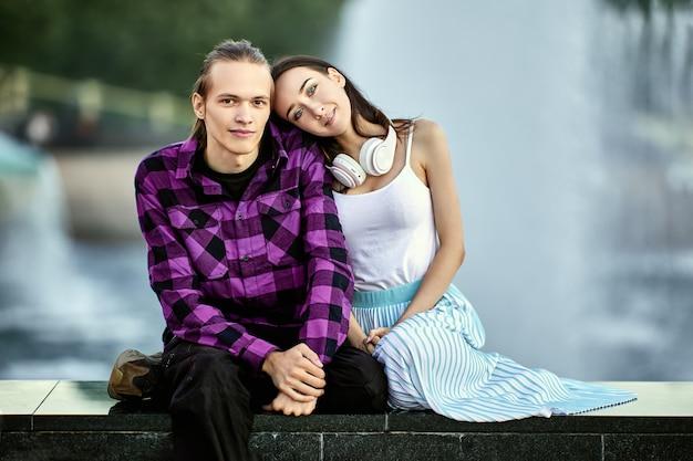 若い男性と女性は、日付の間に公園の噴水の近くに座っています