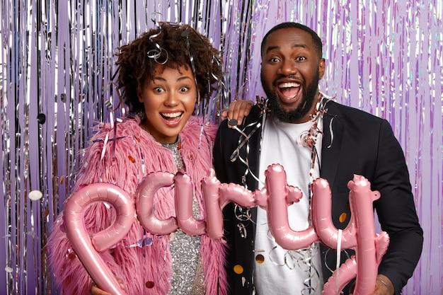 Молодой мужчина и женщина на вечеринке, держа воздушные шары