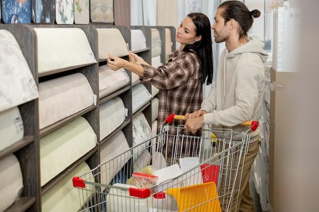 若い男性と女性が自分の家やハードウェアスーパーマーケットのアパートに新しいリノリウムを選ぶ