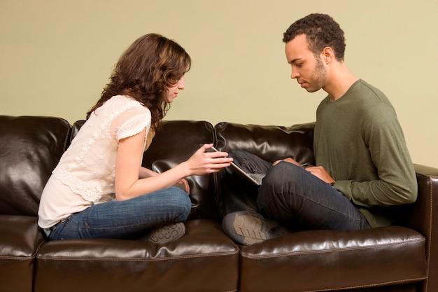 Молодой человек и женщина, вычисляющий на диване
