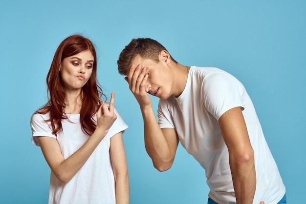明るい青の背景に白いtシャツの若い男性と女性のカップル手の中指