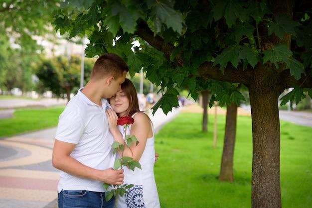 Молодой мужчина и женщина обнимаются на свидании, стоя под деревом
