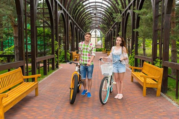 젊은 남녀는 자전거를 타고 공원의 아치 밑에서 자유 시간을 보낸다