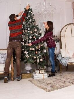 彼らのリビングルームの大きなクリスマスツリーに装飾や装飾品をぶら下げてクリスマスを飾る若い男性と女性