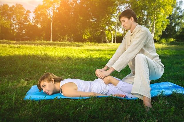 흰 가운을 입은 젊은 남녀가 매트에 누워 요가를 하며 타이 마사지를 하고 있습니다. 백그라운드에서 녹색 잔디와 화창한 여름 공원