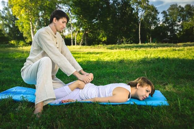 흰 가운을 입은 젊은 남녀가 매트에 누워 요가를 하며 타이 마사지를 하고 있다