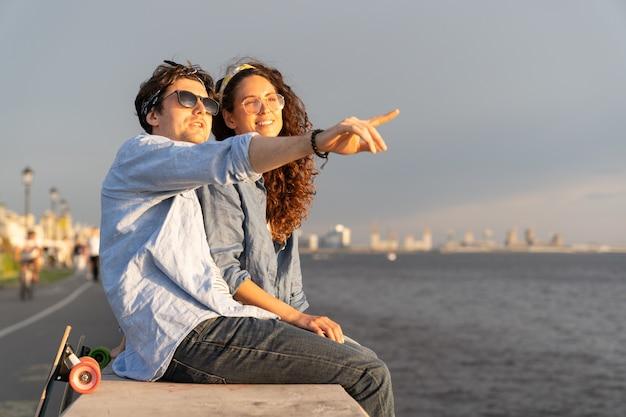 콘크리트 포장도로에 앉아 해변에서 일몰을 즐기는 젊은 남녀가 하늘을 쳐다본다