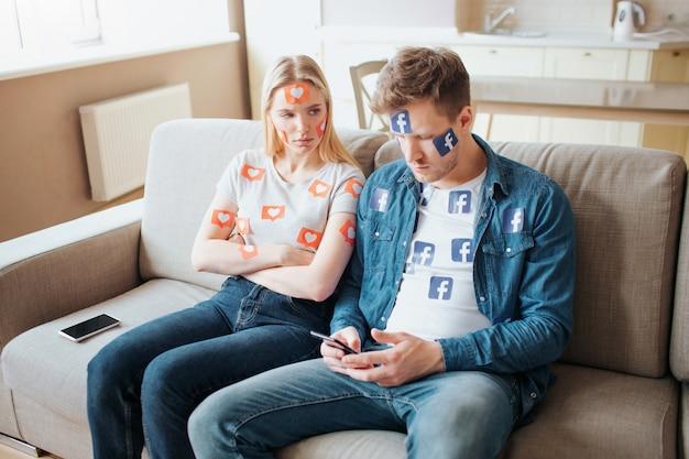 若い男と女はソーシャルメディア中毒です。スマートフォンの中毒性の概念。ソファの上の怒っている女性。