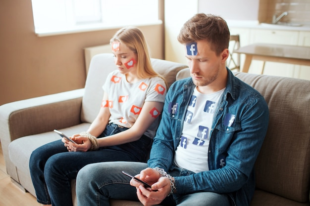 Молодой мужчина и женщина имеют социальную зависимость. сядьте на диван в комнате и посмотрите на телефоны. дневной свет.