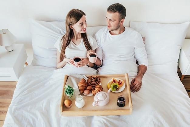 寝室の白いベッドで朝食をとっている若い男性と女性