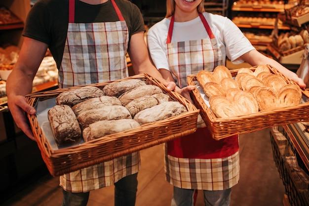 若い男性と女性は手に新鮮なおいしい白い暗いパンのバスケットを持っています。食料品店に立ちます。ビューをカットします。忙しい労働者