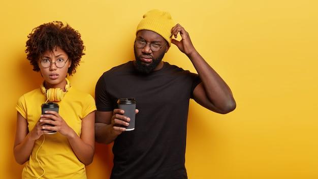 コーヒーのカップを保持している若い男と女