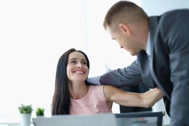 Молодой мужчина и женщина в деловых костюмах, обниматься на работе в офисе. любовные романы на работе концепции
