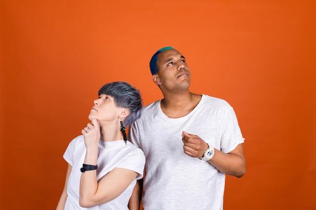 Молодой мужчина и женщина в повседневном белом на оранжевой стене с задумчивым взглядом держатся за подбородок