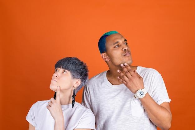 オレンジ色の壁にカジュアルな白を着た若い男女があごを持って思いやりのある表情
