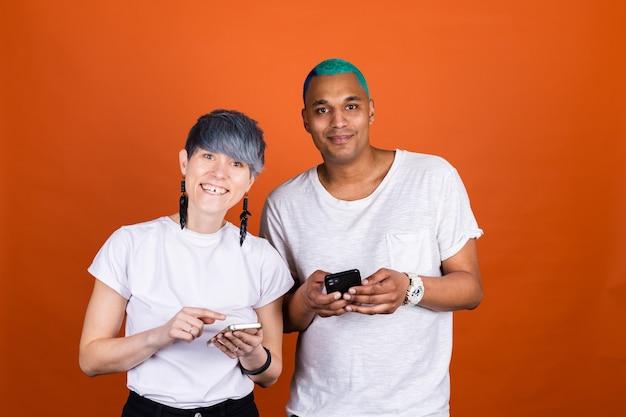 携帯電話の幸せな一緒に笑顔でオレンジ色の壁にカジュアルな白の若い男女