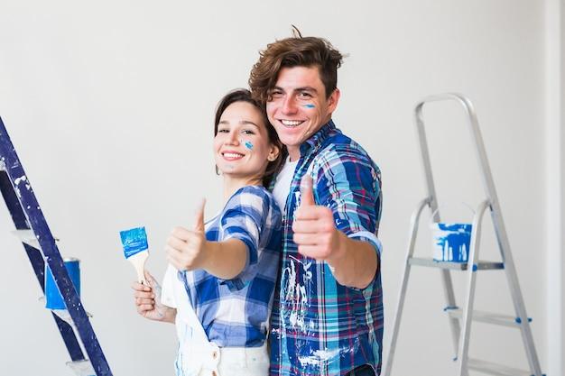 若い男と女が恋をして壁を描き、親指を立てる。