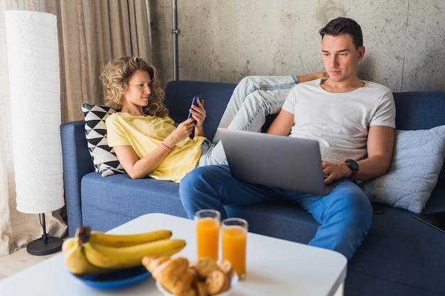 Молодой мужчина и женщина в любви, сидя дома, работая онлайн