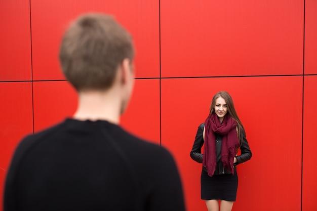 Молодой мужчина и женщина в страсти, эмоциях, на улице на фоне красной стены. мода