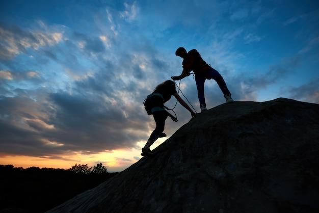 산에서 젊은 남자와 여자. 손으로 돕는 남자와 암벽 등반에 종사하는 밧줄을 가진 여자.