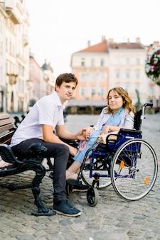 Молодой мужчина и женщина в инвалидной коляске веселиться и улыбаться на скамейке снаружи.