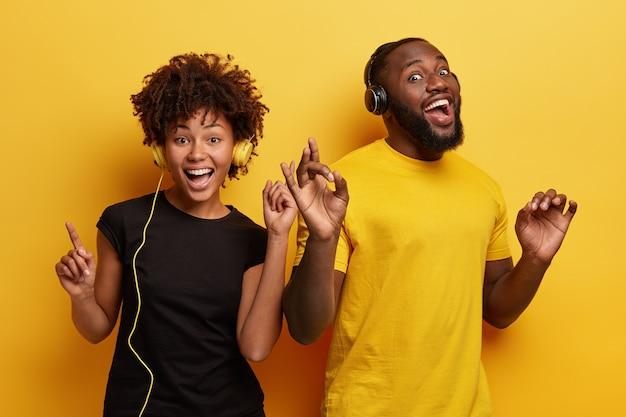 ヘッドフォンで音楽を聴いている若い男性と女性