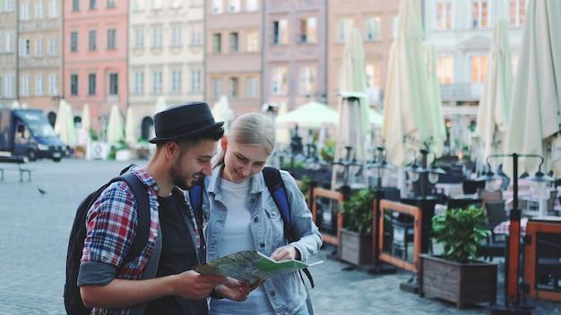 Молодой мужчина и женщина, глядя на основные туристические достопримечательности с помощью карты. они так счастливы осмотреть достопримечательности.