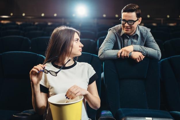 Молодой мужчина и женщина встречаются в кинотеатре перед началом фильма. showtime, индустрия развлечений