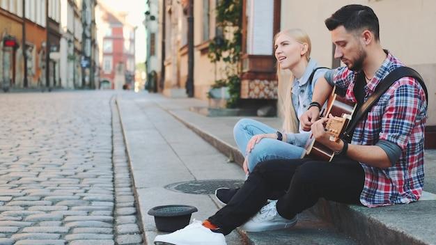 Молодой мужчина и женщина уличных певцов сидят на тротуаре, играют на гитаре и поют. концепция образа жизни.