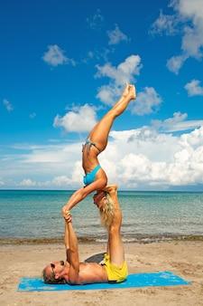 若い男性と女性が一緒にフィットネスヨガの練習を行うビーチで。強度とバランスのためのアクロヨガ要素