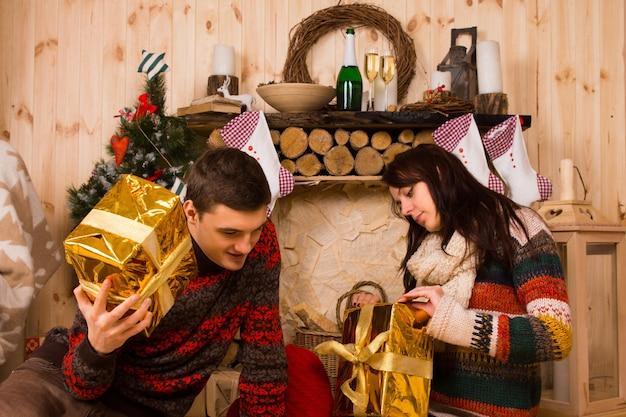 彼らは木造のコテージで一緒にお祝いの季節を祝うように彼らのカラフルな金の装飾的なクリスマスプレゼントを開く若い男性と女性