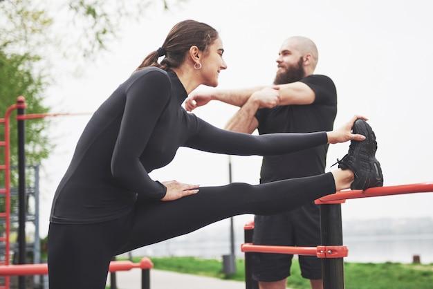若い男性と女性はスポーツをする前に運動とストレッチマークを実行します