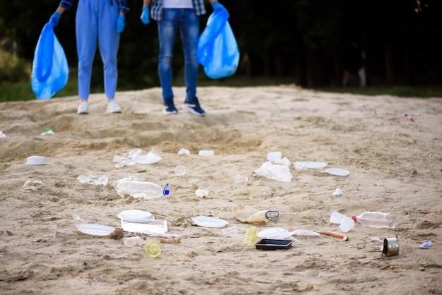 Молодой мужчина и женщина, собирая мусор на открытом воздухе.
