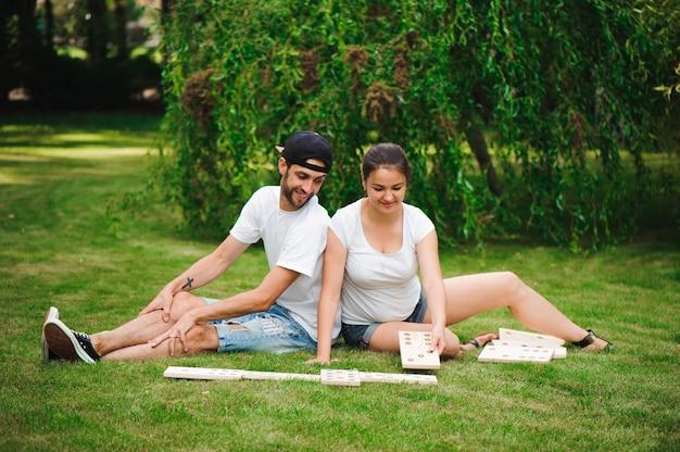 Молодой мужчина и женщина играют в гигантские домино в парке на траве.