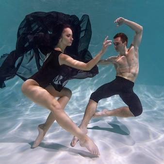 若い男と女が水中に沈んで一緒にポーズをとる