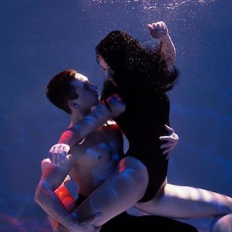 Молодой мужчина и женщина вместе позируют под водой
