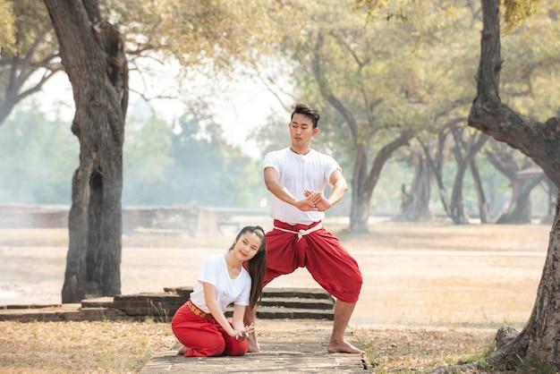 Молодой мужчина и женщина, практикующие традиционный тайский танец