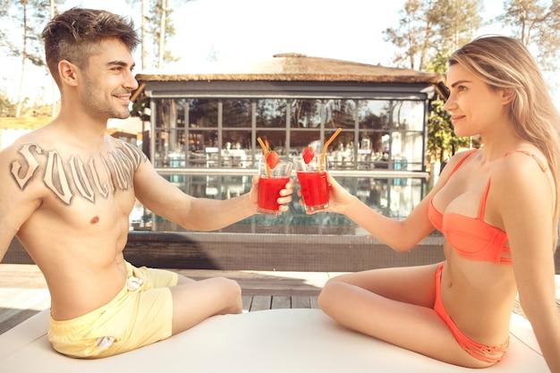 若い男性と女性がカクテルを飲みながらプールの近くで一緒に休む