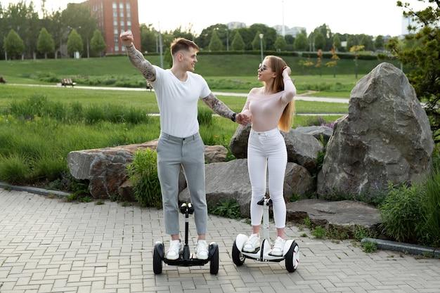 Молодой мужчина и женщина катаются на ховерборде в парке