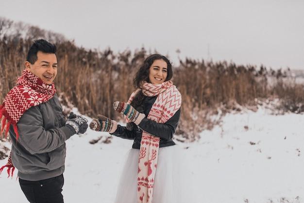 Молодой мужчина и женщина бегут, лежа в снегу, смеются, дурачатся, весело играют в снежки