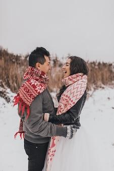 笑って雪の中で横になって走っている若い男と女