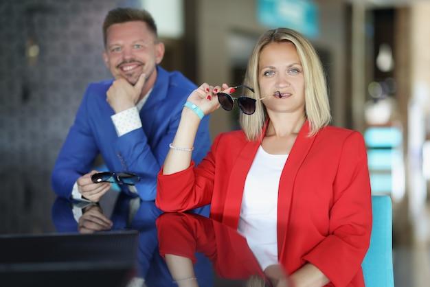 Молодой мужчина и женщина сидят в баре с солнцезащитными очками в руках